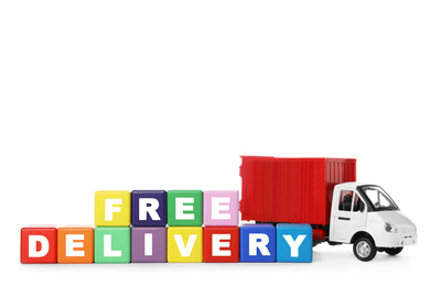 Toy truck and cubes with words FREE DELIVERY isolated on white. Logistics and wholesale concept