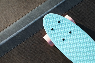 Modern light blue skateboard with pink wheels on ramp outdoors, top view. Space for text