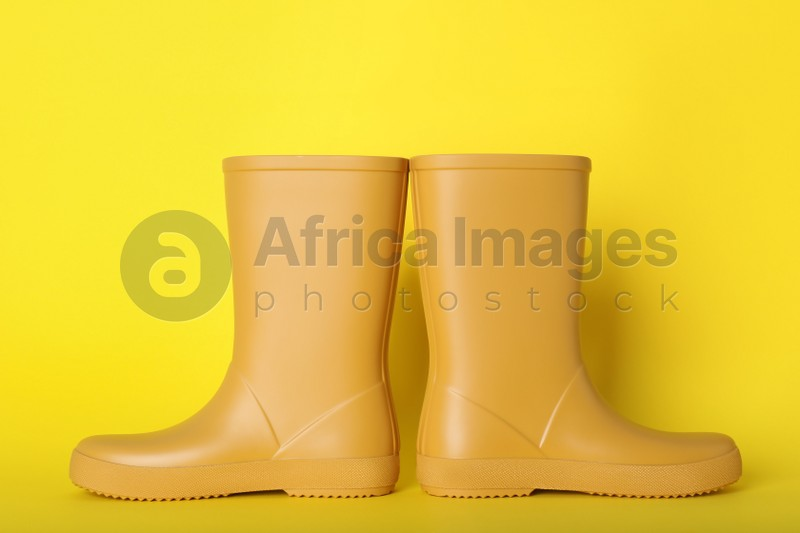 Pair of bright rubber boots on yellow background