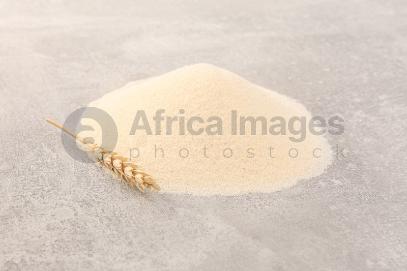 Pile of uncooked organic semolina and spikelet on grey table
