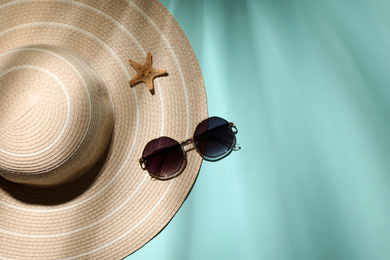 Stylish hat, starfish and sunglasses on light blue background, flat lay with space for text. beach objects