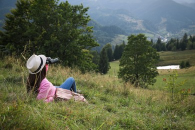 Young woman with binoculars enjoying mountain landscape. Space for text