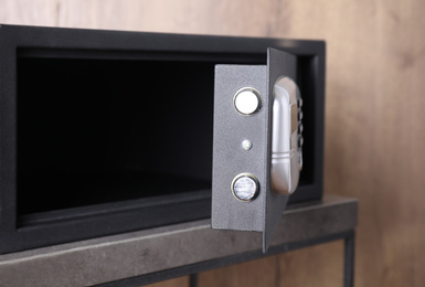 Black steel safe with electronic lock on grey table, closeup