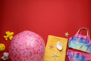 Flat lay composition with ball and beach objects on red background, space for text
