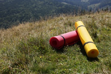 Rolled sleeping pads on grass in mountains, space for text