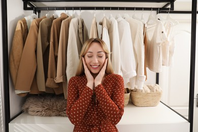 Happy young woman near rack with different clothes in dressing room