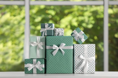 Many beautifully wrapped gift boxes on white table  near window