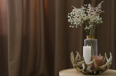 Vase with beautiful flowers and candles on table indoors, space for text. Interior elements