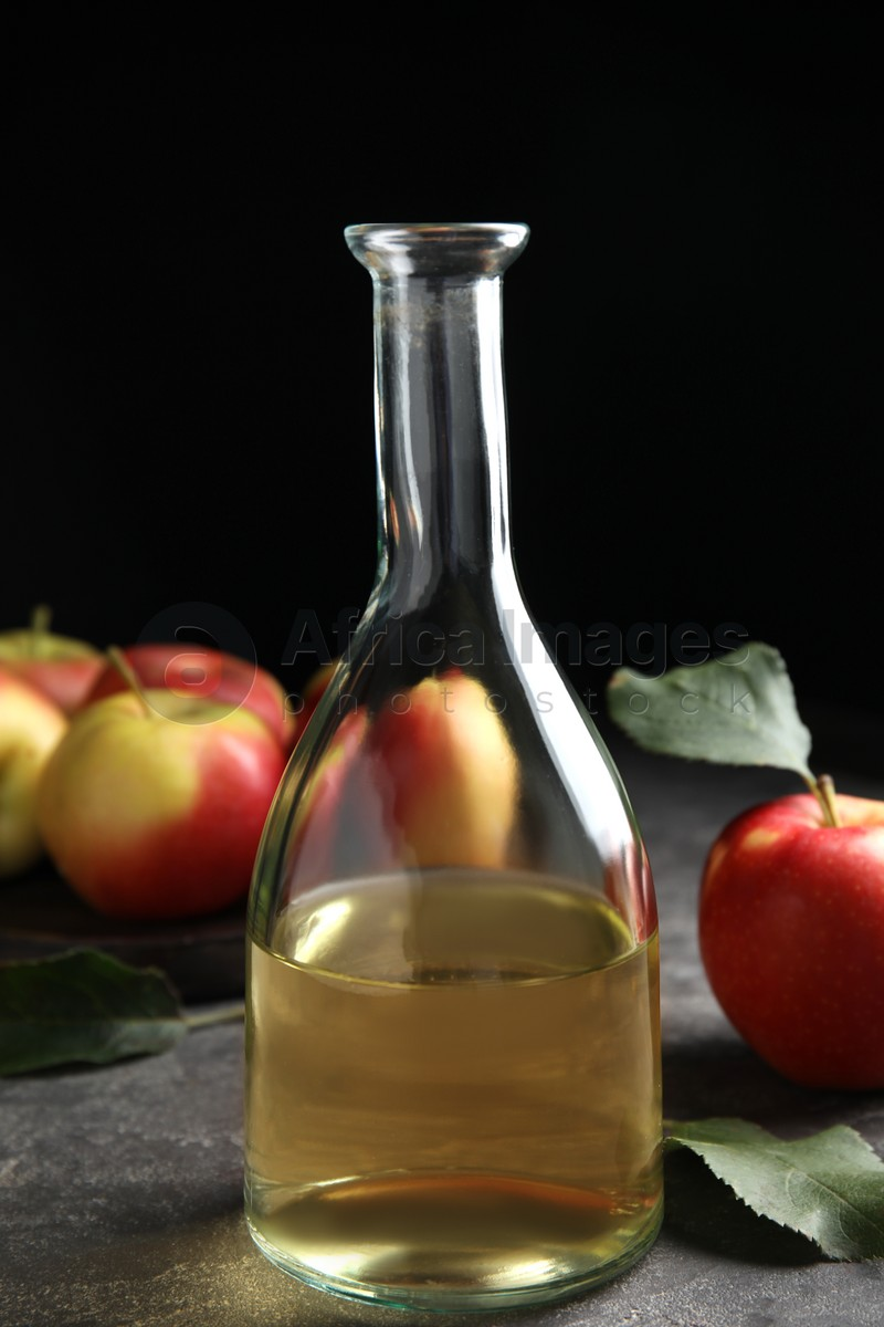 Natural apple vinegar and fresh fruits on grey table