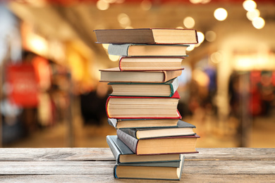 Collection of different books on wooden table against blurred background