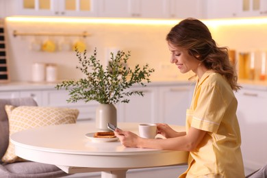 Beautiful young woman with smartphone having breakfast in kitchen. Weekend morning