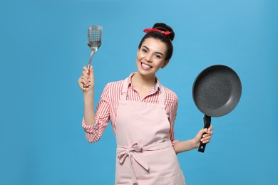 Housewife with frying pan and spatula on light blue background