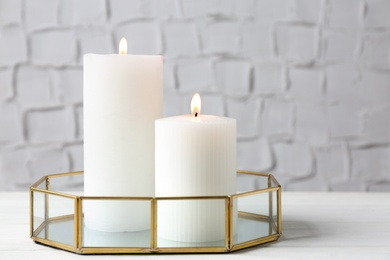 Tray with burning candles on white table indoors