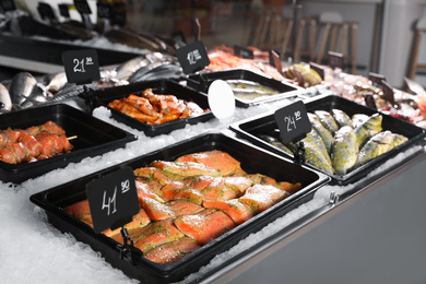Different types of marinated fish on ice in supermarket
