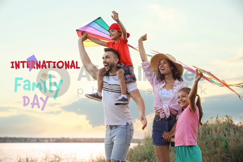 Happy parents and their children playing with kites outdoors. Happy Family Day