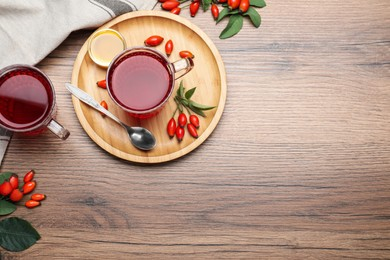 Fresh rose hip tea, honey and berries on wooden table, flat lay. Space for text