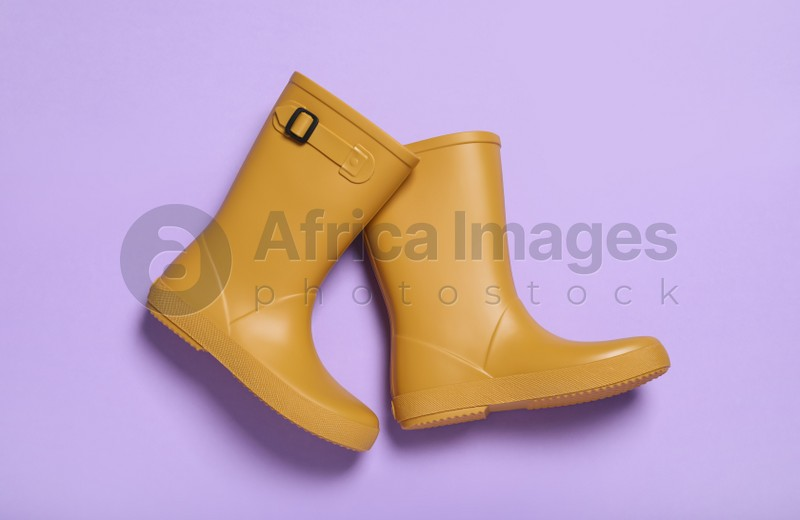 Pair of yellow rubber boots on violet background, top view