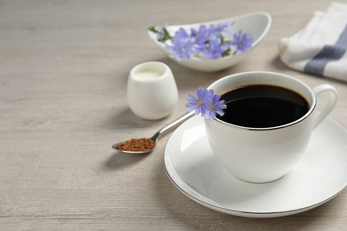 Cup of delicious chicory drink and flowers on light wooden table, space for text