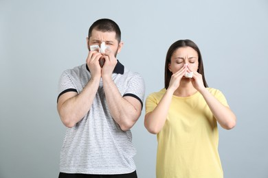 Man and woman with tissues suffering from runny nose on light grey background
