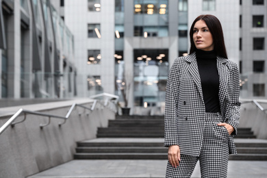 Portrait of beautiful woman in stylish suit on city street. Space for text