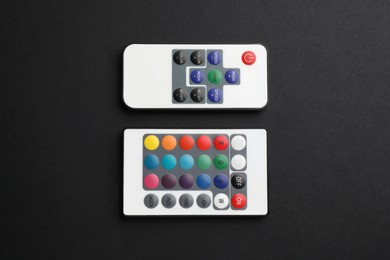 Remote controls on black background, flat lay