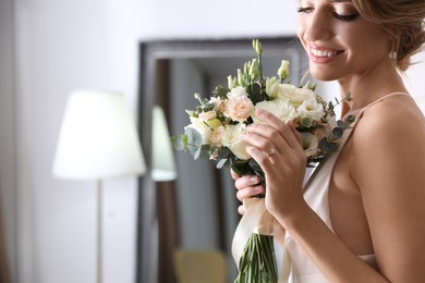 Young bride with beautiful wedding bouquet indoors