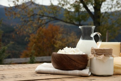 Tasty cottage cheese and other fresh dairy products on wooden table in mountains. Space for text