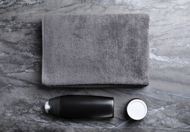 Towel, shower gel and cream on grey marble background, flat lay. Men's cosmetics