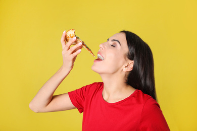 Beautiful woman eating tasty pizza on yellow background