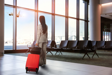 Businesswoman with bag and travel suitcase at airport terminal. Summer vacation