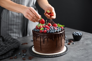 Woman decorating delicious chocolate cake with fresh strawberries at table, closeup