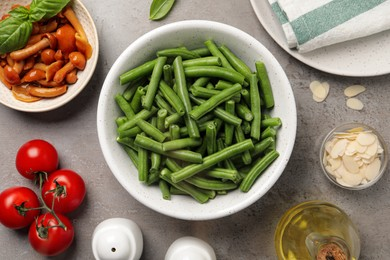 Fresh green beans and other ingredients for salad on grey table, flat lay