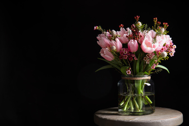 Beautiful bouquet with spring pink tulips on wooden table against black background. Space for text