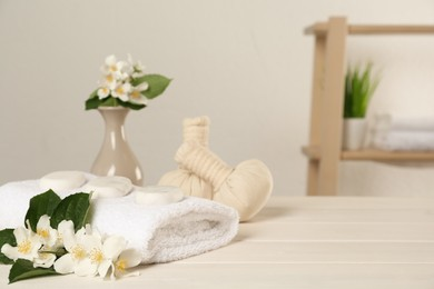 Beautiful jasmine flowers, towel, spa stones and herbal bags on white wooden table indoors, space for text