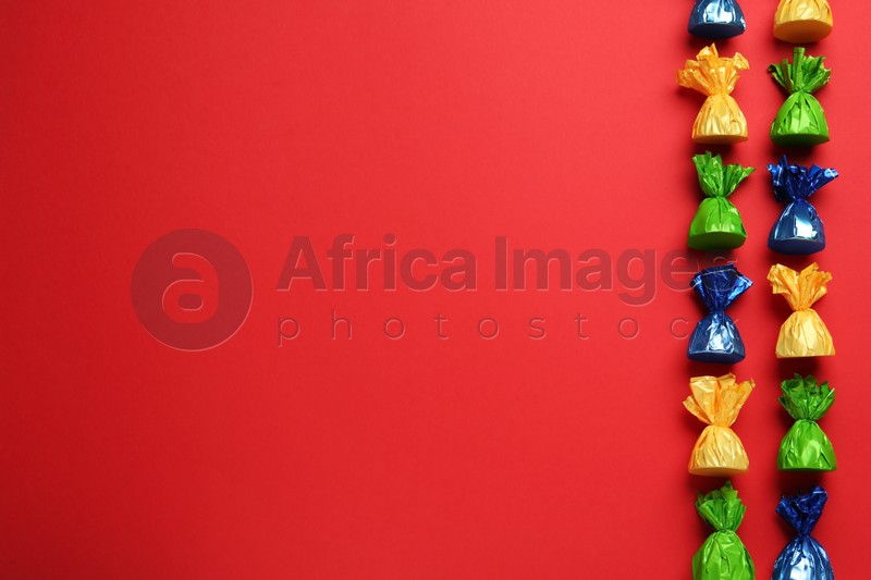 Many candies in colorful wrappers on red background, flat lay. Space for text