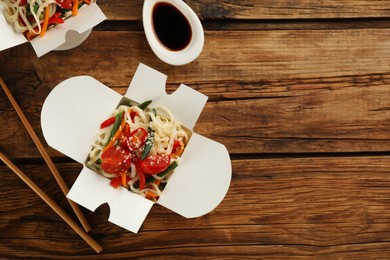 Box of vegetarian wok noodles with chopsticks and soy sauce on wooden table, flat lay. Space for text