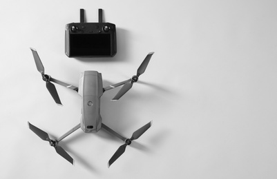 Modern drone with controller on light background, top view. Space for text