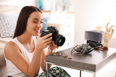 Young photographer taking picture of jewelry indoors