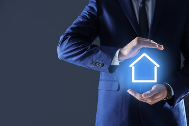 Property insurance concept. Man demonstrating house image, closeup