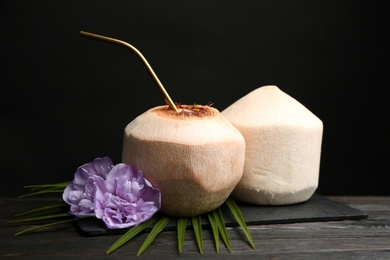 Fresh  coconuts with drinking straw and flowers on wooden table against black background