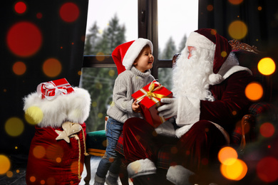 Santa Claus giving Christmas gift to little boy near window indoors