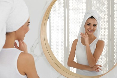 Happy young woman with clean skin looking at mirror in bathroom