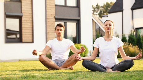 Sporty couple practicing morning yoga at backyard. Healthy lifestyle