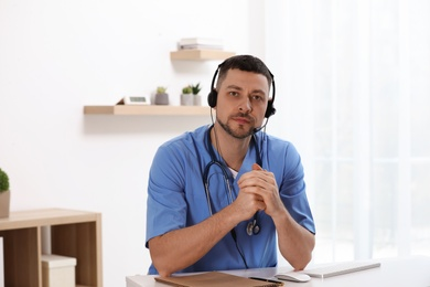 Doctor with headset sitting at desk in clinic. Health service hotline