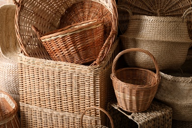 Many different wicker baskets made of natural material as background, closeup