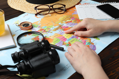 Woman with world map at table, closeup. Travel during summer vacation