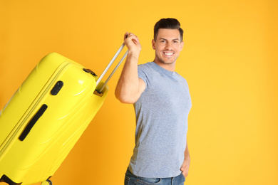 Handsome man with suitcase for summer trip on yellow background. Vacation travel
