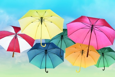Group of different colorful umbrellas against blue sky on sunny day