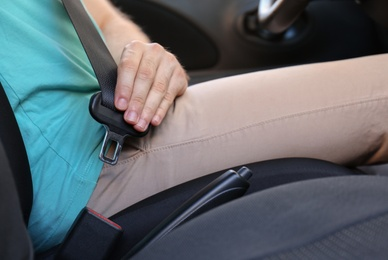 Man fastening safety belt on driver's seat in car, closeup