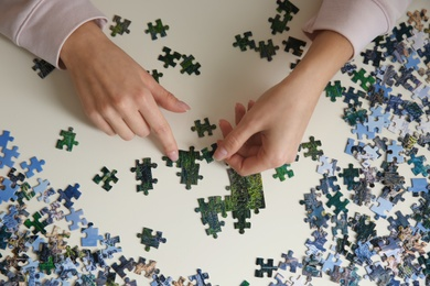 Young woman playing with puzzles at table, top view